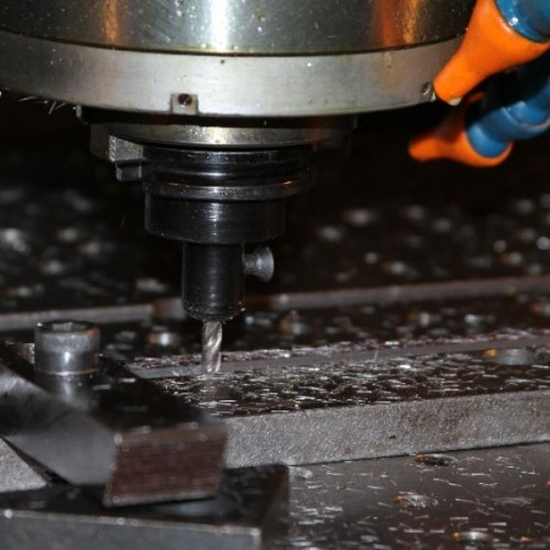 CNC machine being used to drill hole in fabricated metal bar